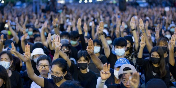 Pro-democracy activities raise a three-fingers, symbol of resistance salute during a protest at Democracy Monument in Bangkok, Thailand, Sunday, Aug, 16, 2020. Protesters have stepped up pressure on the government demanding to dissolve the parliament, hold new elections, amend the constitution and end intimidation of the government's opponents. (AP Photo/Gemunu Amarasinghe)